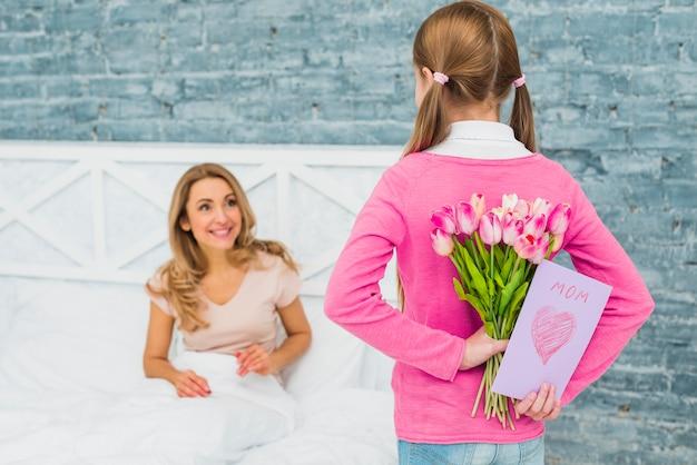 Filha segurando o cartão e tulipas para a mãe na cama Foto gratuita