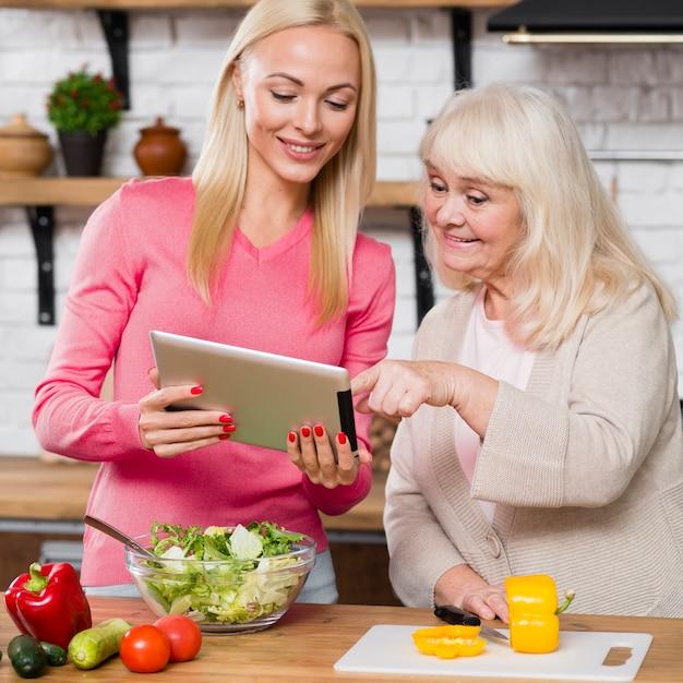 Filha segurando o tablet digital e rolagem mãe Foto gratuita