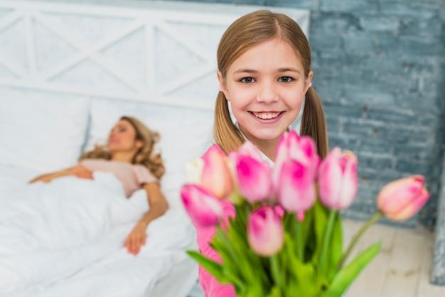 Filha, segurando, tulips, para, dormir, mãe Foto gratuita