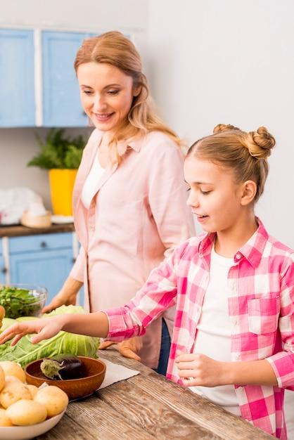 Filha sorridente ajudando a mãe na cozinha Foto gratuita
