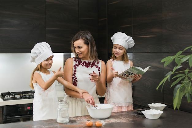Filhas felizes usando chapéu de chef com mãe preparando comida na cozinha Foto gratuita