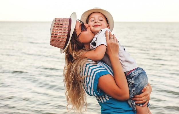 Filhinho nos braços, abraça a mãe à beira-mar Foto Premium