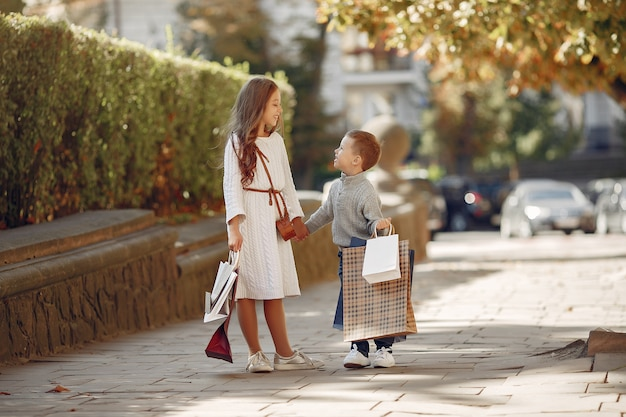 Filhinhos bonitos com sacola de compras em uma cidade Foto gratuita