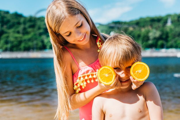 Filhinhos, brincando com fatias de laranja na praia Foto gratuita