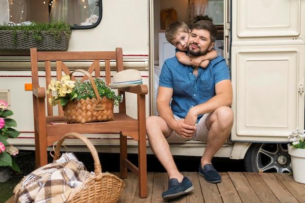 Filho abraçando o pai enquanto está sentado na caravana Foto gratuita