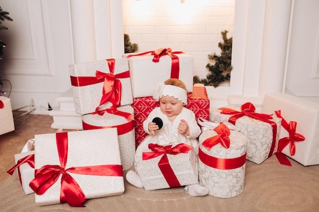 Filho bonito vestido branco posando debaixo da árvore de natal. Foto Premium