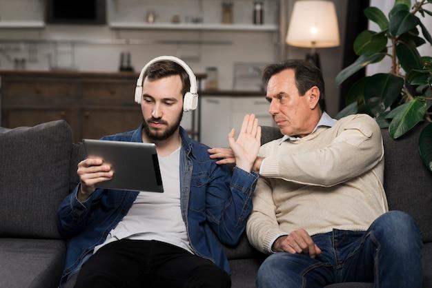 Filho com fones de ouvido e tablet, ignorando o pai Foto Premium