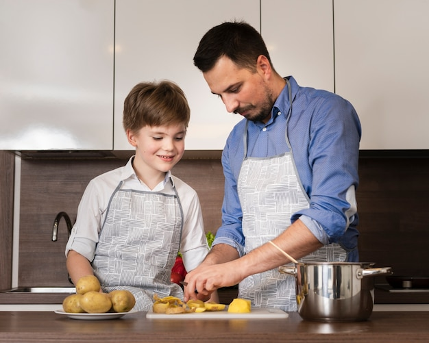 Filho de ângulo baixo, ajudando o pai a cozinhar Foto gratuita