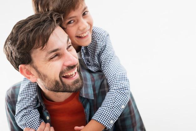 Filho de vista frontal, abraçando seu pai Foto gratuita