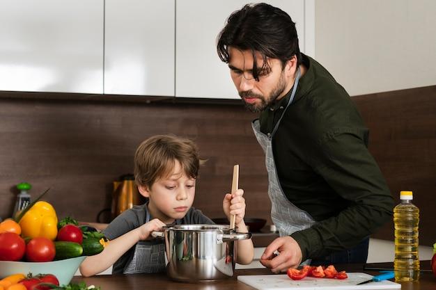 Filho de vista frontal e pai cozinhar Foto gratuita