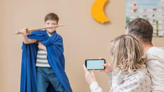 Filho fazendo um show para o dia dos pais como cavaleiro Foto gratuita
