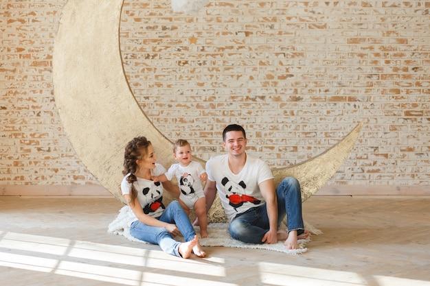 Filho feliz do pai, da mãe e da criança da família perto de uma parede de tijolo vazia na sala. Foto gratuita