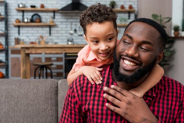 Filho negro abraça pai por trás Foto gratuita