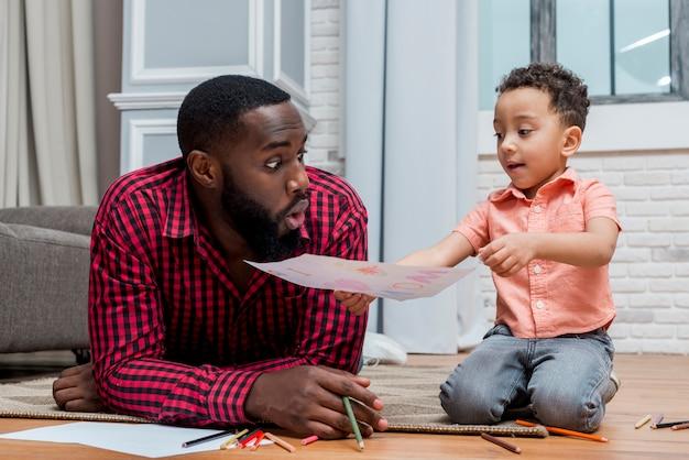Filho negro mostrando desenho para pai espantado Foto gratuita