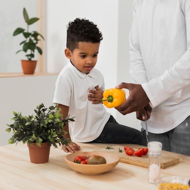 Filho, olhando para o pai fazendo o jantar Foto gratuita