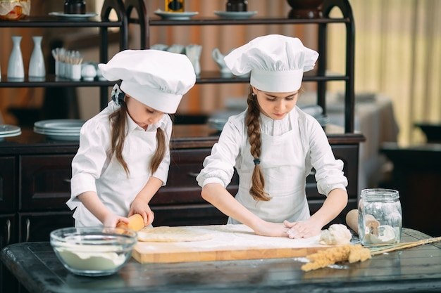 Filhos de garotas engraçadas estão preparando a massa na cozinha. Foto Premium