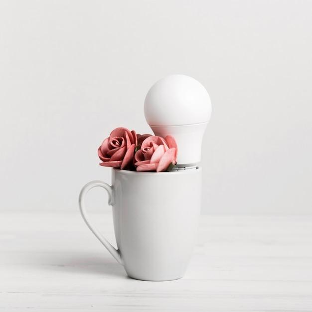 Filhote com lindas rosas e uma lâmpada Foto gratuita