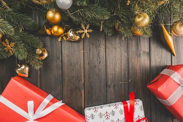 Filiais do pinho com decorações do natal em placas de madeira com presentes embaixo Foto gratuita