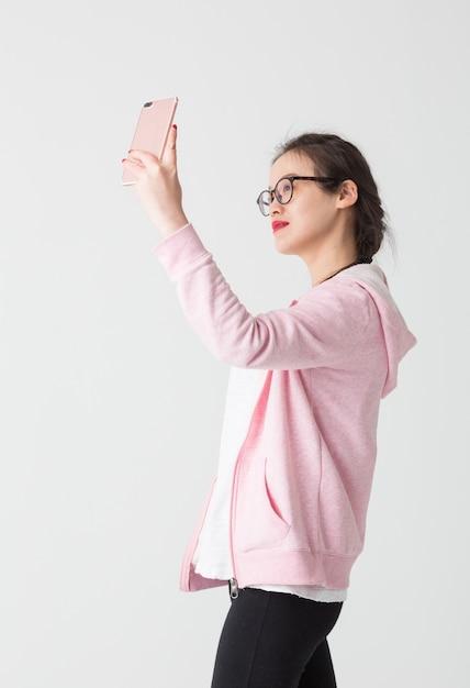 Filmado no estúdio de jovens asiáticas no uso da empresa de telefonia móvel Foto gratuita