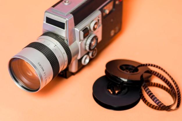 Filmadora com película de filme em pano de fundo colorido pêssego Foto gratuita
