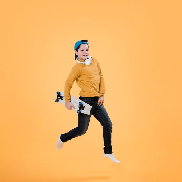 Filmagem completa de menino moderno com skate Foto gratuita