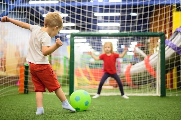 Filmagem completa do menino chutando bola Foto gratuita