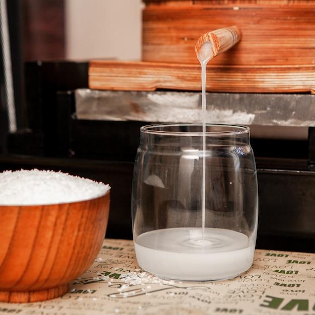 Filtrando suco de coco em uma vista lateral da jarra de vidro Foto gratuita