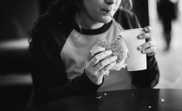 Fim, cima, adolescente, menina, comer, hambúrguer, obesidade, conceito Foto gratuita