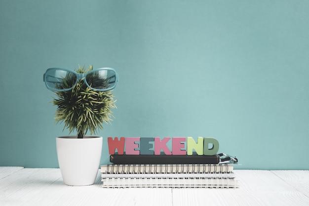 Fim de semana texto e papel de caderno e pequena árvore na madeira Foto Premium