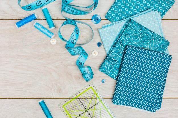 Fio azul; fita métrica; botões; régua e roupas de impressão dobradas na mesa de madeira Foto gratuita
