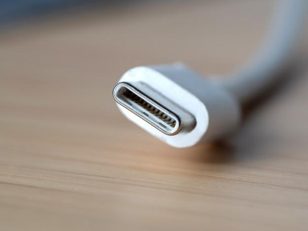 Fio branco tipo c close-up sobre uma mesa de madeira. novo conector usb para dispositivos portáteis Foto Premium