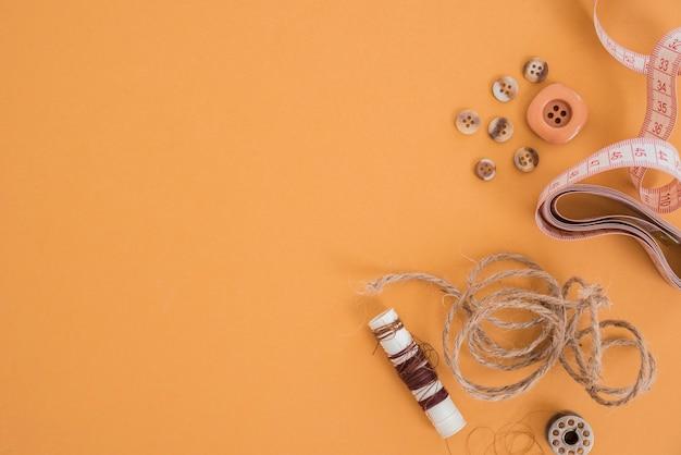 Fio de juta; botão; fita métrica e carretel em fundo colorido Foto gratuita