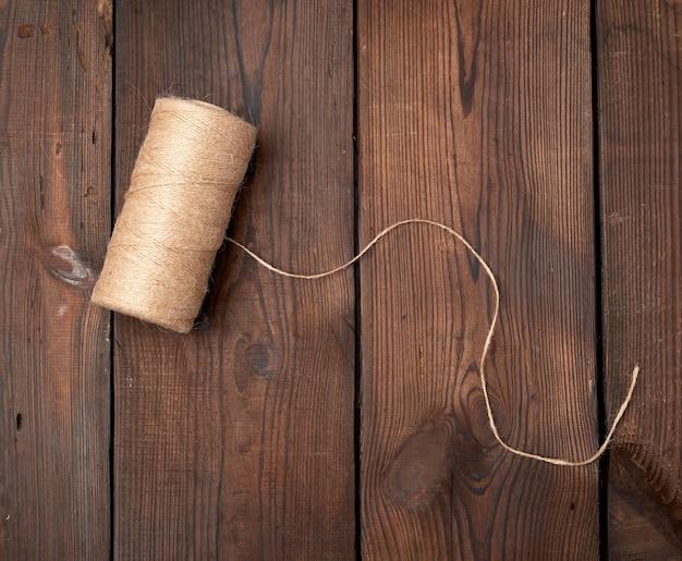 Fio marrom torcido em um carretel em uma mesa de madeira Foto Premium