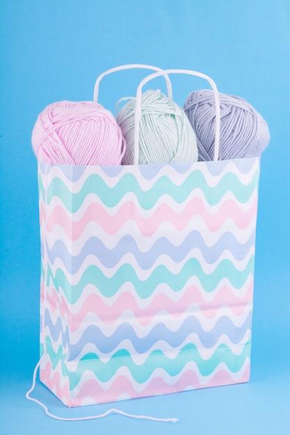 Fio para tricotar delicadas cores pastel em um saco de papel multicolorido sobre um fundo azul. Foto Premium