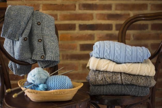 Fios e roupas quentes em cadeiras Foto gratuita