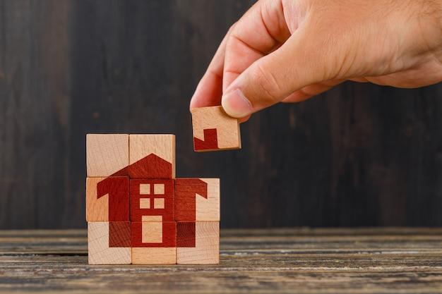 Fique em casa conceito na vista lateral da mesa de madeira. mão segurando o cubo de madeira. Foto gratuita