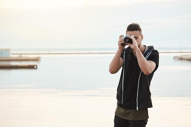 Fique onde está, esta foto é incrível. retrato do fotógrafo freelancer bonito criativo, olhando através da câmera enquanto tira fotos da natureza e das pessoas, em pé perto da beira-mar Foto gratuita