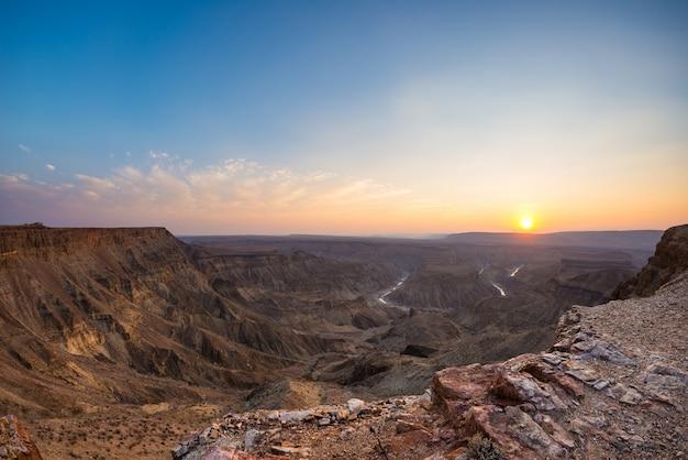 Fish river canyon, destino de viagem cênica no sul da namíbia. última luz solar nos cumes das montanhas. visão de grande angular de cima. Foto Premium