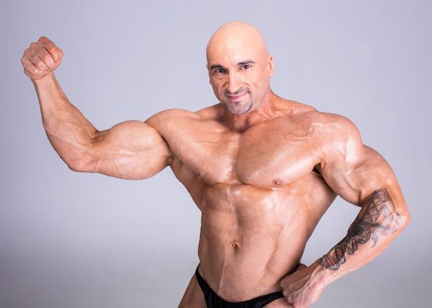 Fisiculturista está demonstrando seu corpo musculoso perfeito. Foto Premium