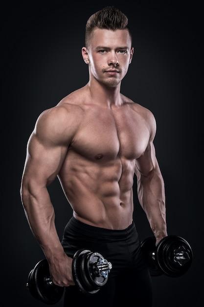 Fisiculturista fazendo exercícios com halteres Foto Premium