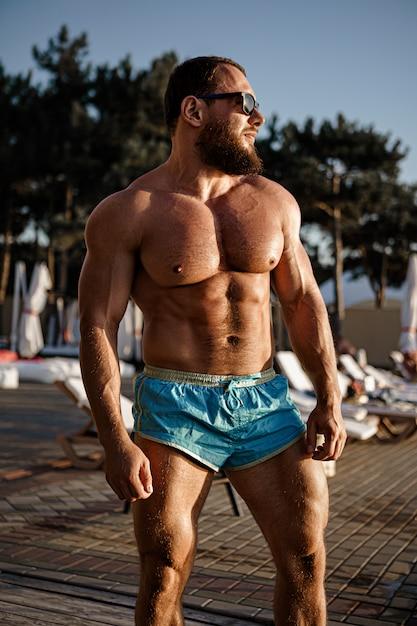 Fisiculturista homem musculoso bronzeamento em um clube de praia Foto Premium