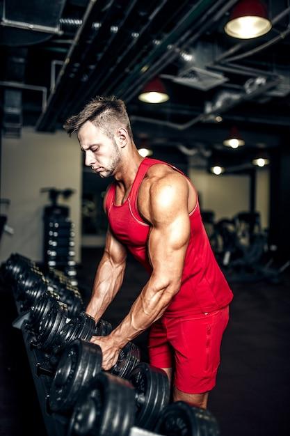 Fisiculturista levantando halteres pretos pesados no ginásio. Foto Premium