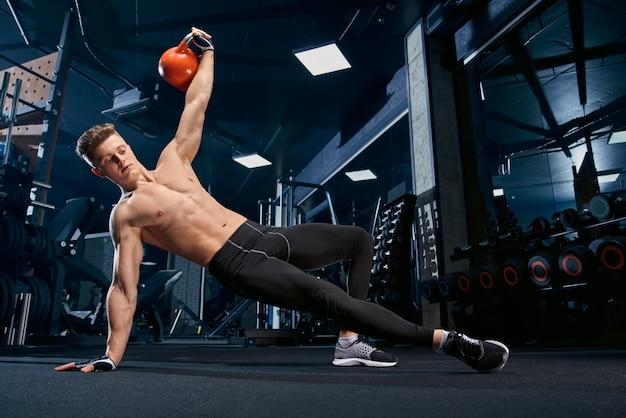 Fisiculturista sem camisa, fazendo exercícios de prancha lateral. Foto gratuita