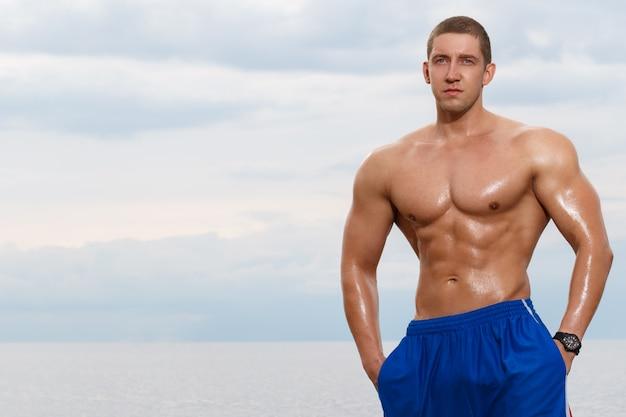 Fisiculturista sexy na praia Foto gratuita