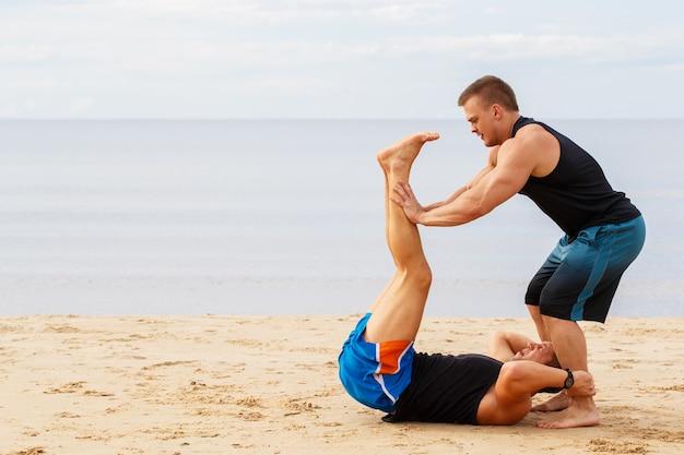 Fisiculturistas na praia Foto gratuita
