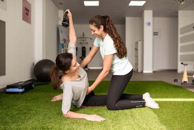 Fisioterapeuta ajudando jovem caucasiana com exercício com haltere Foto gratuita