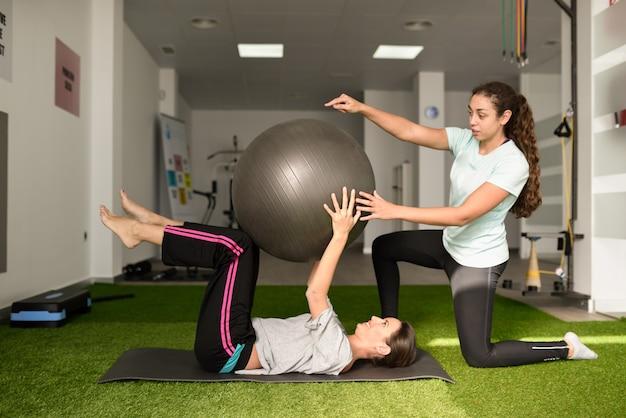 Fisioterapeuta ajudando jovem caucasiana com exercício Foto gratuita