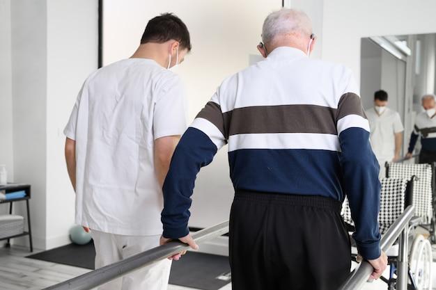 Fisioterapeuta ajudando paciente idoso a caminhar entre barras paralelas. Foto Premium