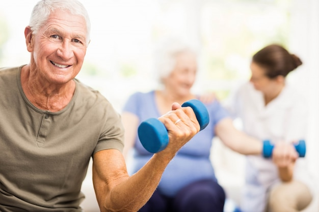 Fisioterapeuta ajudando pacientes com exercícios em casa Foto Premium