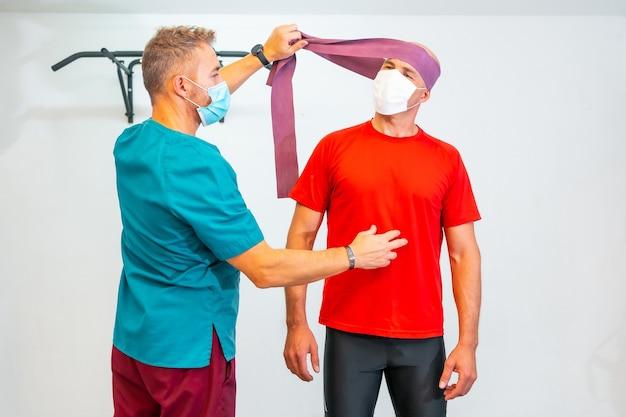 Fisioterapeuta com máscara facial esticando o pescoço do paciente com elástico. fisioterapia com medidas de proteção para a pandemia de coronavírus, covid-19. osteopatia, quiromassagem esportiva Foto Premium
